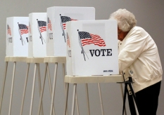 A voter casts her vote in a voting booth, Tuesday, Nov. 4, 2014, in Thornton, Colo. (AP Photo/Jack Dempsey)